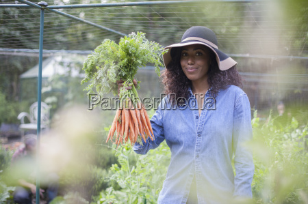 woman holding up carrots from allotment