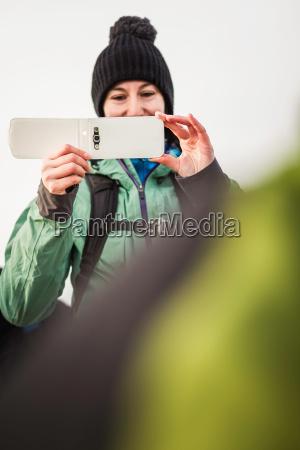 hiker taking pictures in rural landscape