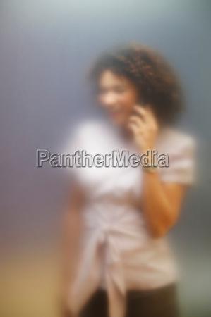 woman on phone behind screen