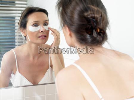 woman in bathroom applying a face
