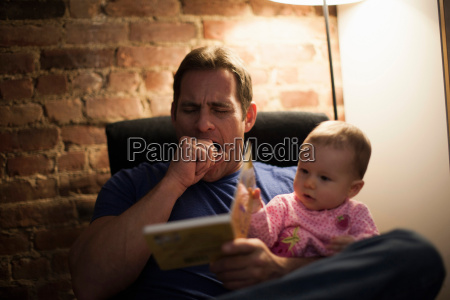tired father reading to baby daughter