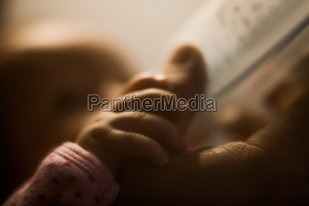 baby girl holding fathers thumb