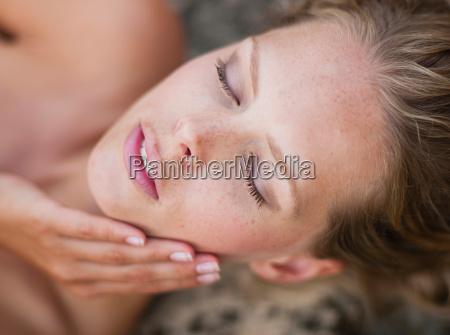 woman lying on rocks eyes closed