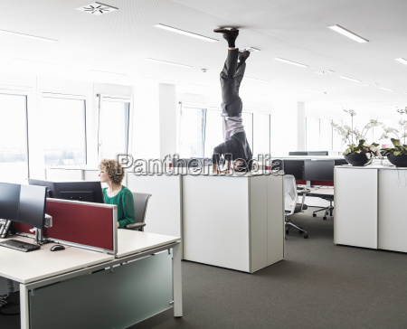 businessman doing headstand on filing cabinet
