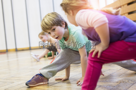 children stretching legs bent leaning forwards