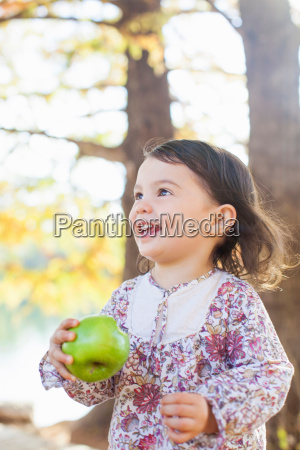 child with toothy smile holding green