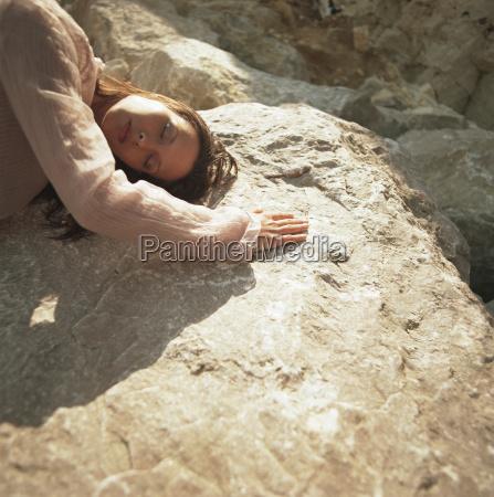 woman lying on warm rock