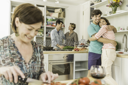 five adult friends preparing food and