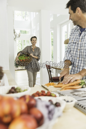 couple carrying and preparing fresh vegetables