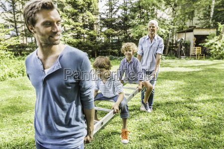 mature man with son carrying grandsons