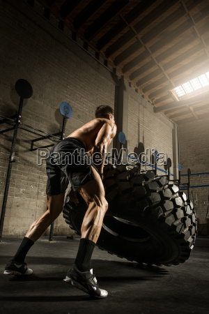 young man lifting large tyre in