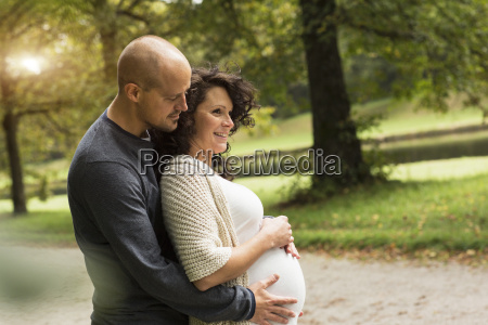 pregnant couple caressing belly in park