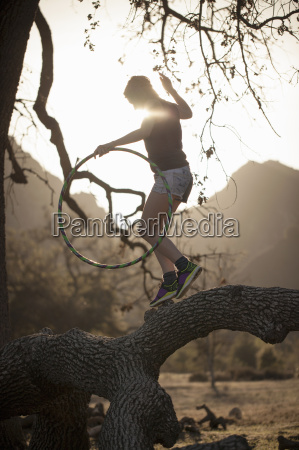 young woman balancing on branch with