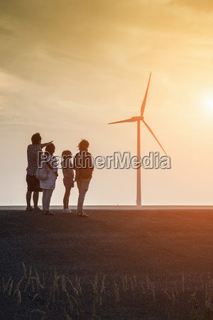 family group looking at wind turbines