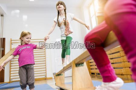 girl holding hands helping friend across
