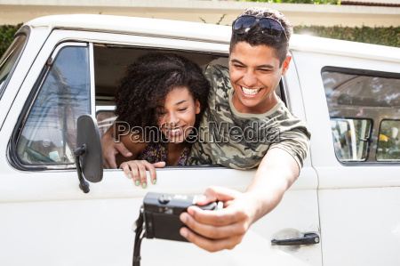 couple taking photograph from inside van
