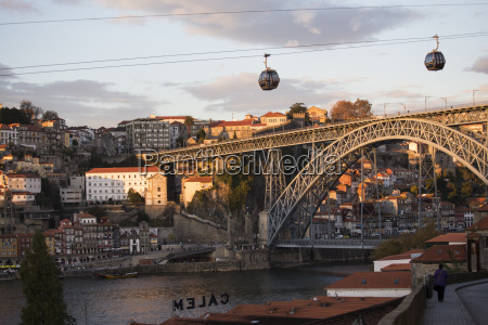 cable cars over river with bridge