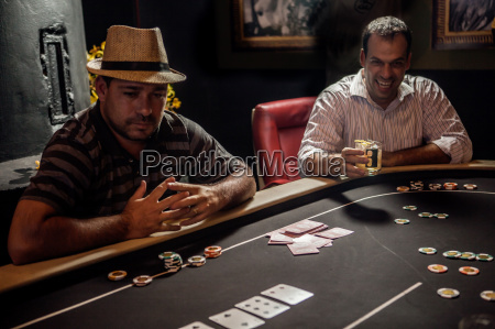 mid adult men playing poker and