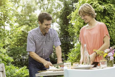 mature man preparing food for young