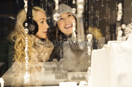 two mid adult women window shopping