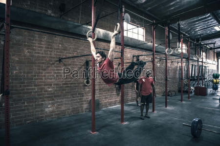 young male crossfitter swinging on gym