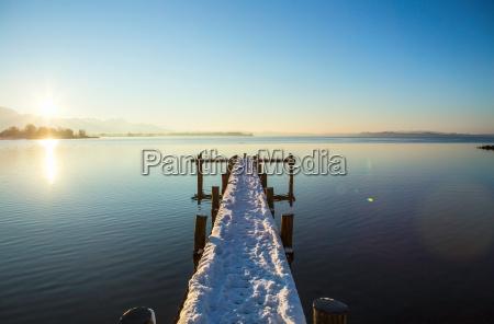 snowy pier over still rural lake