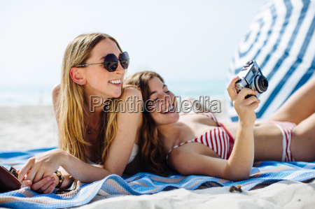 two young female friends sunbathing and
