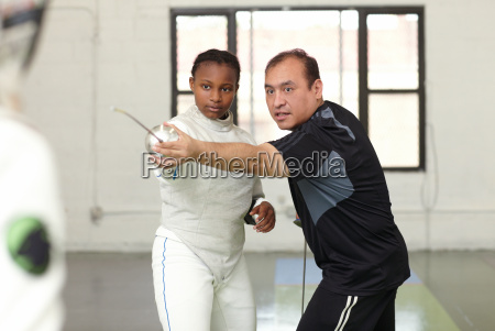 fencing tutor assisting female student