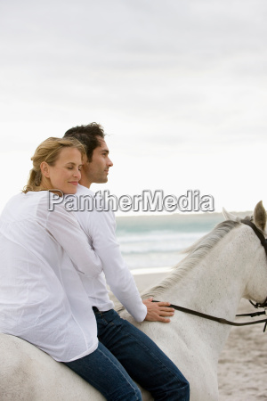 couple with horse on the beach
