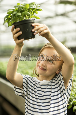 girl holding up potted basil plant