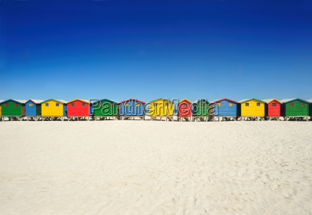 brightly colored beach huts on beach