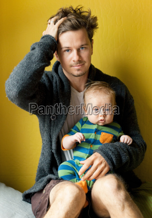 tired father holding baby boy