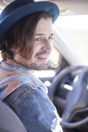 young man sitting in car wearing