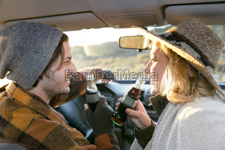 young couple in car holding bottles