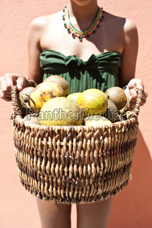 woman holding a basket of coconuts