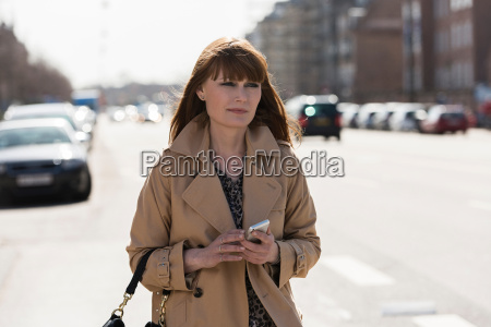 woman with mobile phone walking down
