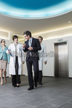 four mid adults walking through lobby