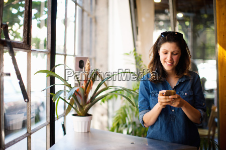 mid adult woman using cellphone indoors