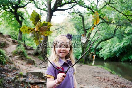 girl holding an oak branch in