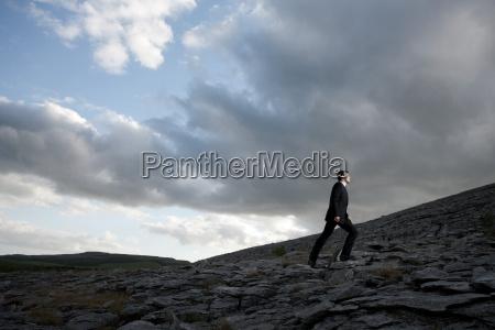 businessman climbing rocky hill