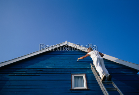 a man painting the weatherboarding of