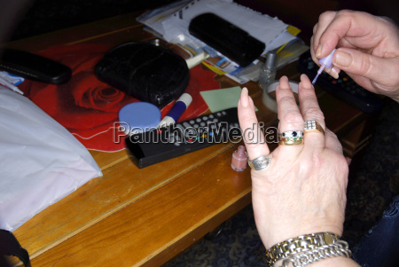 senior woman painting fingernails with nail