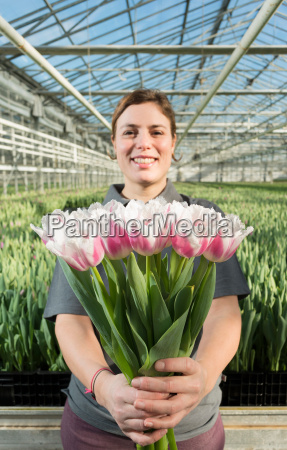 woman holding bunch of pink tulips