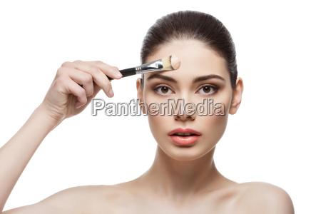 beautiful girl applying foundation with brush