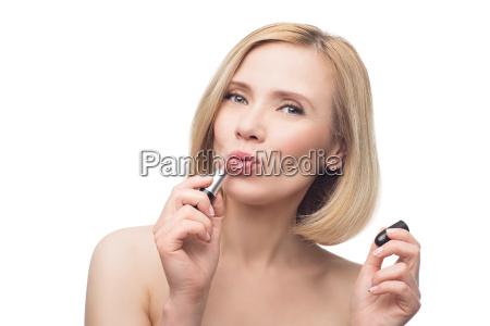 beautiful middle aged woman applying lipstick