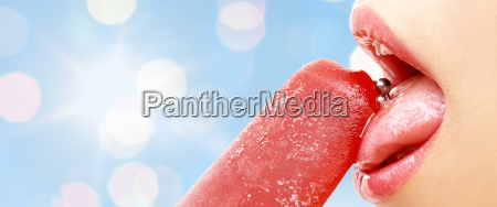 woman with pierced tongue licking fruit