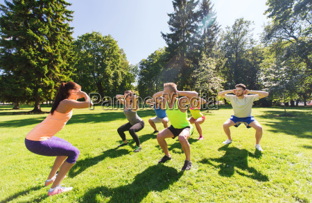 group of happy friends exercising outdoors