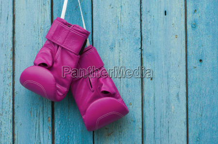 pink boxing gloves on blue cracked