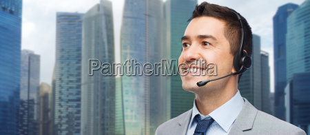 happy businessman in headset over city