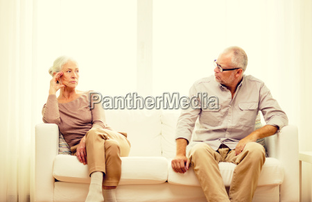 senior couple sitting on sofa at
